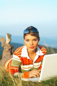Young business woman relaxing, working on laptop computer on meadow